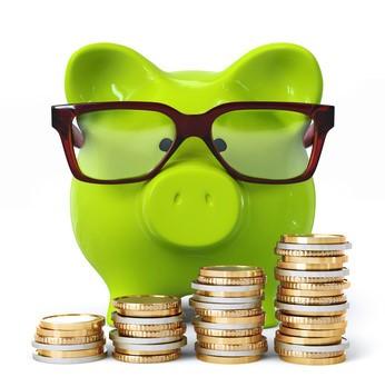 Grünes Sparschwein mit Brille vor Münzstapeln
